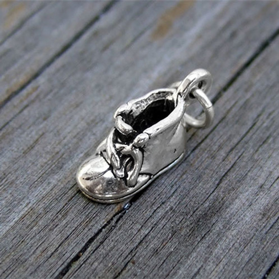 Sterling silver Baby Shoe Charm, shown on wood