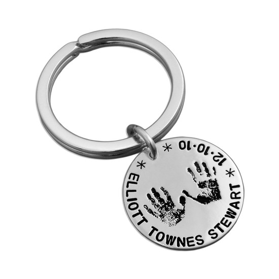 Child's hand prints on a custom sterling silver key ring, with a hand stamped message, shown close up on white