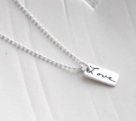 """Dainty Custom SIlver Handwriting Tag necklace, personalized with loved one's handwritten word """"Love"""", shown from the side"""