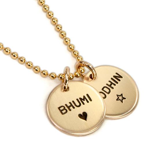 Hand stamped custom Gold Name Discs necklace personalized with kids' names, shown from the side on white