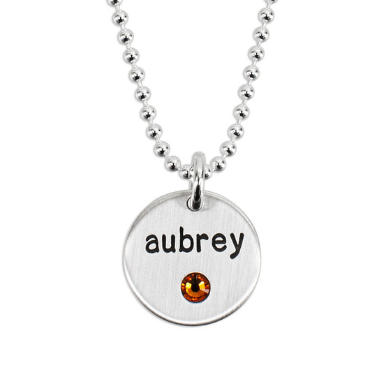"""Silver Disc with Crystal Birthstone Necklace, personalized with hand stamped child's name """"Aubrey"""" in block lower font, shown on white"""