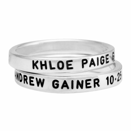 Hand stamped sterling silver stackable rings, personalized with kids names and birth dates, shown close up on white