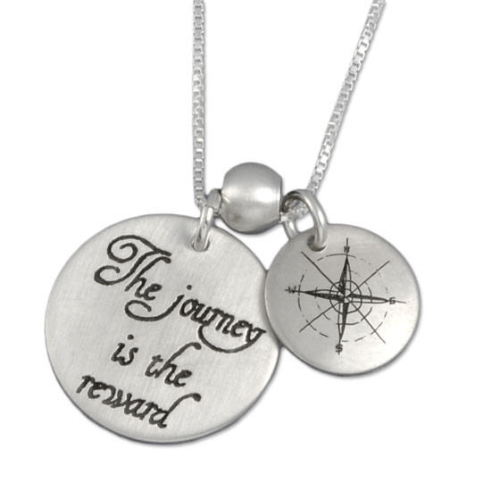 """Custom sterling silver necklace with """"The Journey is the Reward"""" stamped in script, with another charm showing compass points, shown close up on white"""