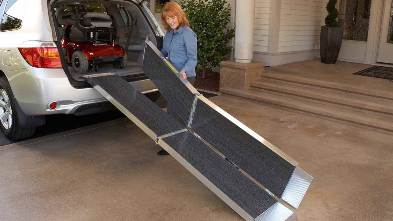 EZ-Access AS Portable Trifold Wheelchair ramp shown being placed at the rear cargo area of a van