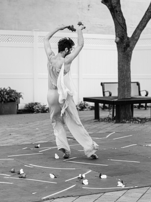 Male dancer in a garden setting with flowers strewn on the ground