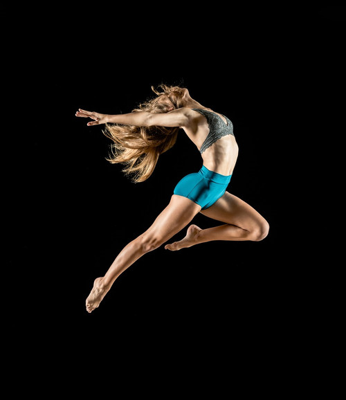 A female dancer in full flight with blue shorts and grey top and arms outstretched