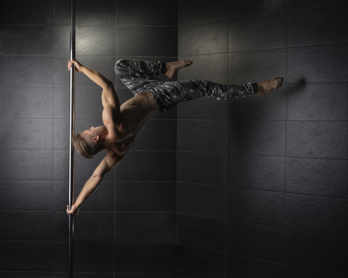 Male pole dancer on a stainless steel pole
