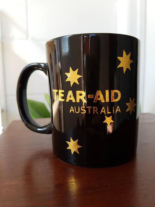 Black ceramic coffee mug with Gold Tear Aid Australia Silver logo