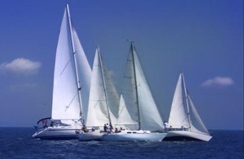 Four yachts with white sails and crews on the sea