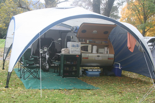 Motor bike, green canvas folding chairs  and open camper under white dome tent