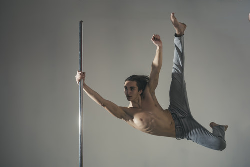 Barefoot male dancer wearing blue jeans in mid air with one arm on a chrome pole