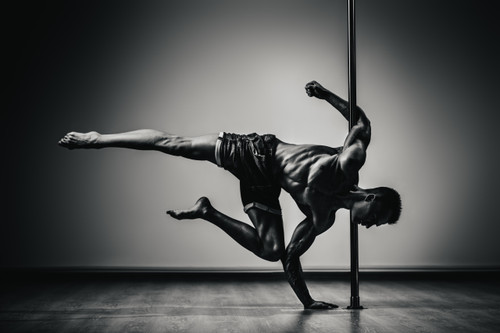 Barefoot male dancer with legs raised and one arm on a stainless steel pole the other arm on the floor