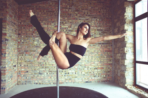 Female pole dancer wearing black shorts, top and leg warmers on a pole with arm outstretched