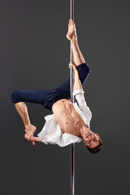 Barefoot male dancer wearing a white shirt and blue trousers on a stainless steel pole