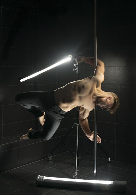 Male dancer holding light sabre on a chrome pole