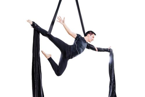 Male dancer suspended on black aerial silk