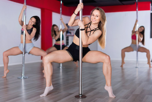 Female pole dancer leaning to the right with three female dancers behind her in pole dance studio setting