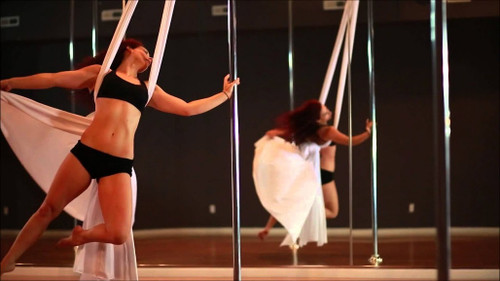 Female dancer in black shorts and top suspended on white aerial silk