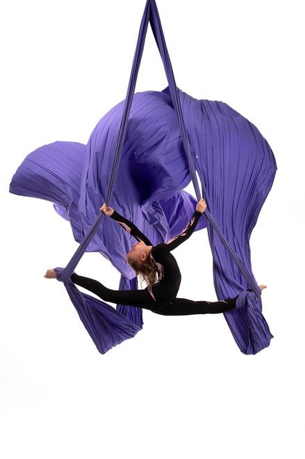 Female dancer suspended on purple aerial silk