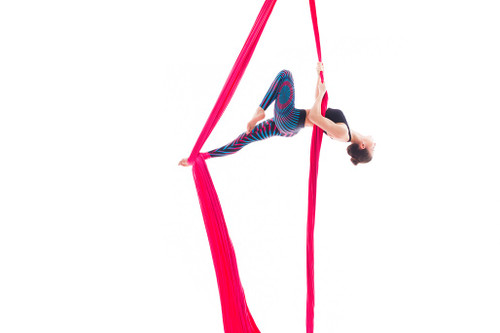 Female dancer suspended on pink aerial silk