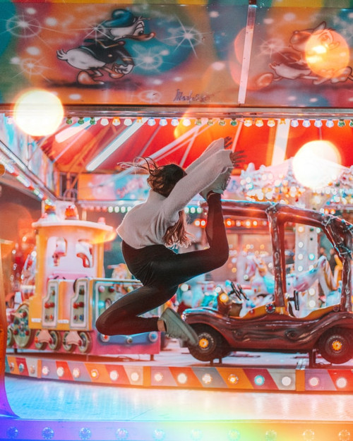 Female dancer with long sleeved sweater and tights leaping in the air with a carnival backdrop