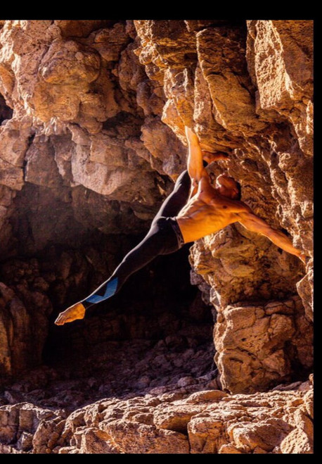Male dancer (Saulo Sarmiento) with black stretch pants suspended from a rocky outcrop