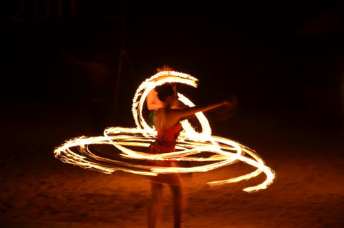Female dancer in a red sequinned outfit with spinning fire lit torch