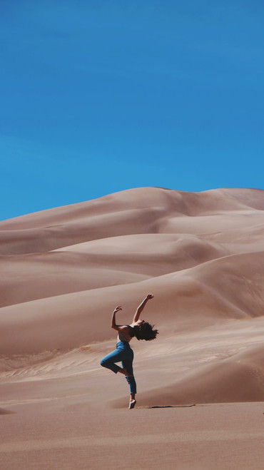 Female dancer wearing blue jeans standing on one leg on a sand dune with bright blue sky