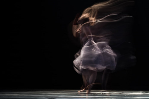 Stylised image of a female dancer spinning with flowing hair and skirt
