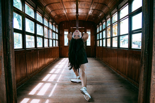 Female dancer with white ballet shoes inside an old train carriage