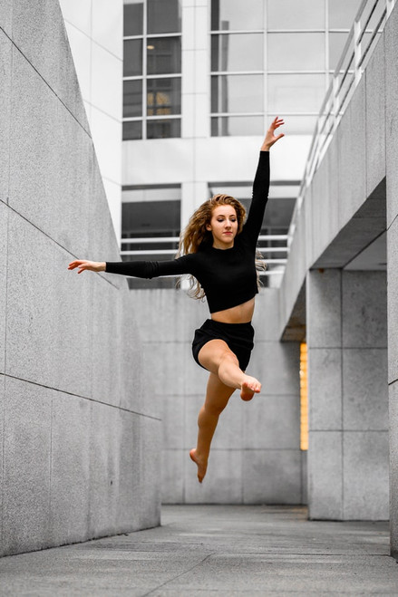 Female dancer with black top and shorts leaping in the air between  grey concrete blocks