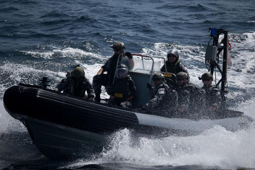 Seven crewmen at sea aboard a rigid hulled inflatable boat