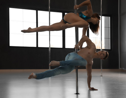 Male and female pole dancers on a pole with two poles in the background