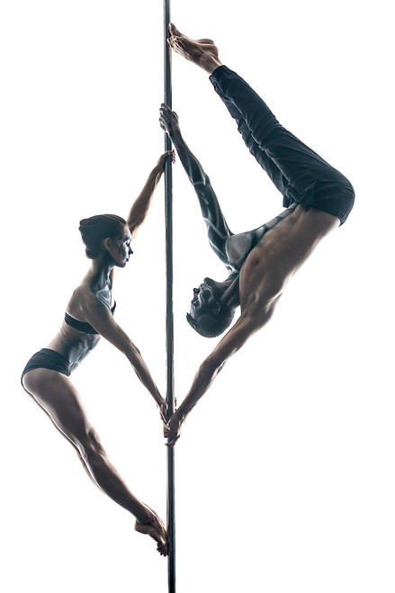 Male and female pole dancers with painted bodies on a pole