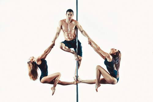 Two female pole dancers holding onto each arm of a male pole dancer balancing on a pole