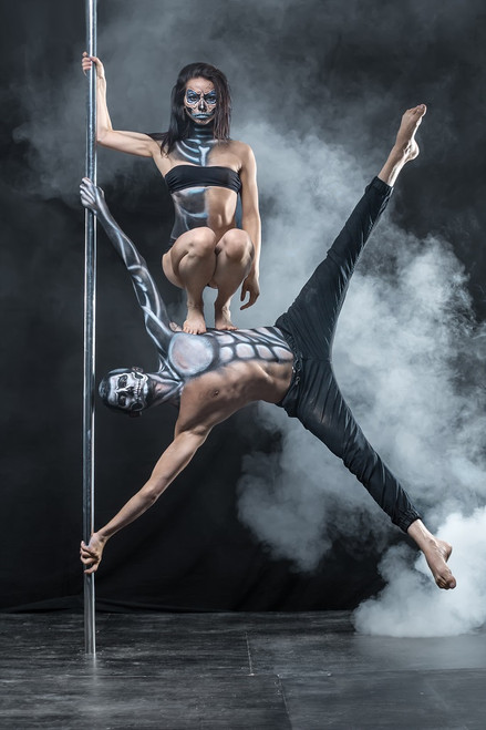 Male dancer horizontal on a pole with a female dancer kneeling on his side, both with skeletal painted bodies