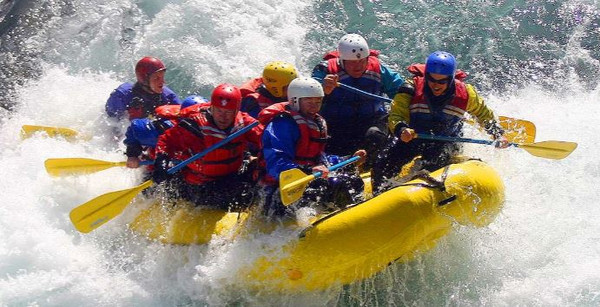 Six people with oars in yellow inflatable whitewater raft