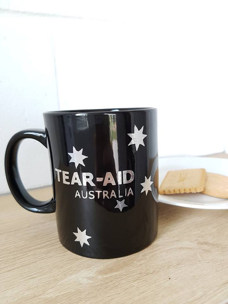 Black ceramic coffee mug with silver Tear Aid Australia logo 1