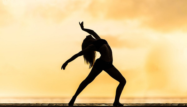 Silhouette of a female dancer leaning back with arms outstretched on golden background