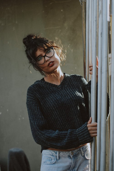 Female in knitted sweater and blue jeans holding onto poles
