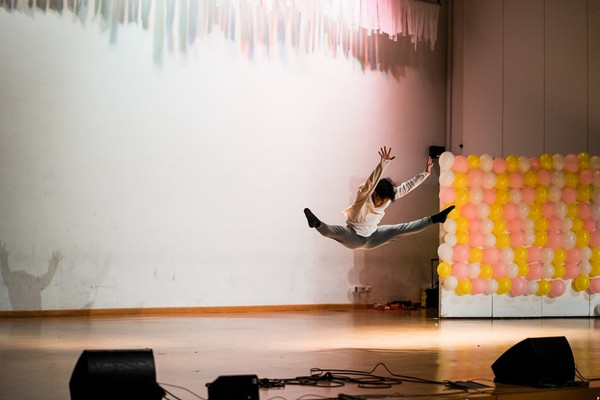 Male dancer with grey pants black socks and white long sleeved top leaping in the air on a stage