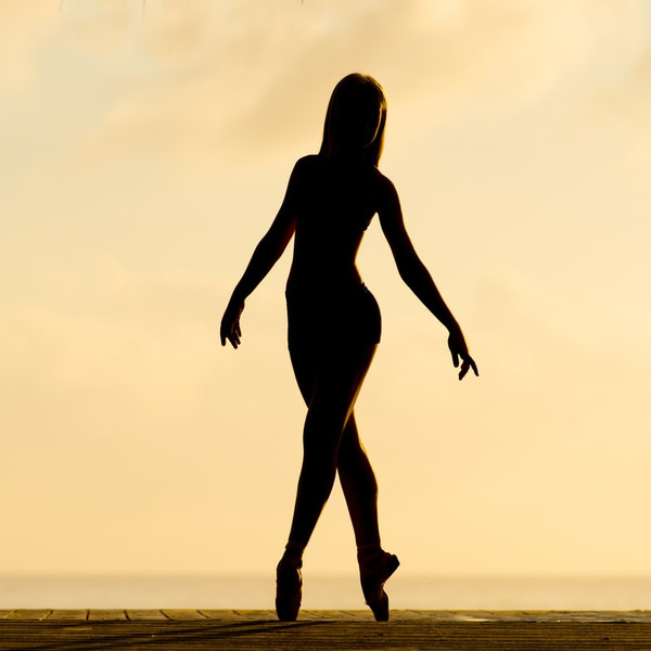 Shadow image of a female dancer on a dark sepia background