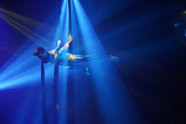 Strong male dancer with arms bent backwards holding onto navy blue aerial silk fabric