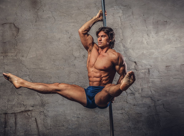 Male pole dancer wearing navy blue shorts hanging on to a pole with legs extended in front him