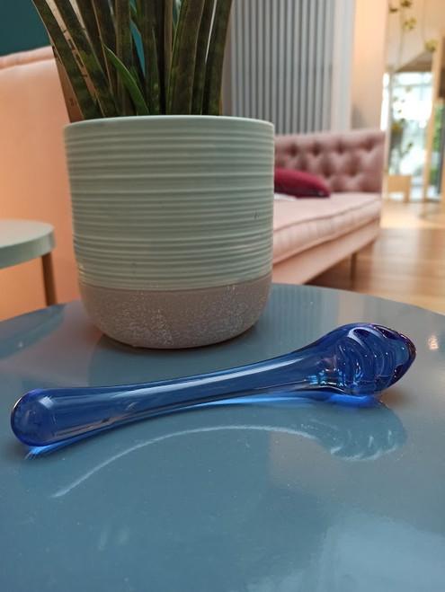 Bibi glazen dildo naast een plant op een salonstafel