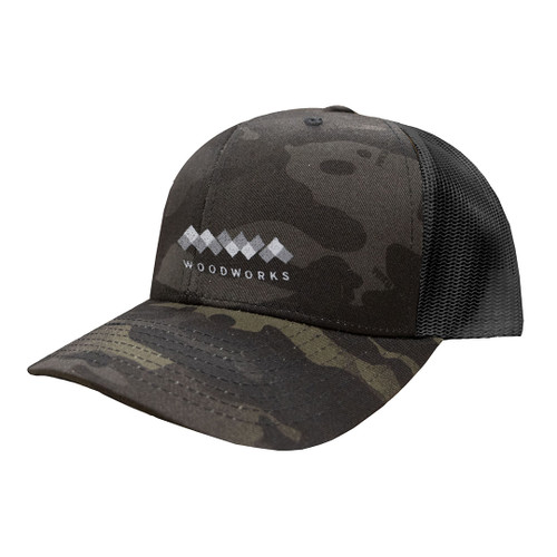 Light MWA Woodworks logo embroidered on dark camo trucker hat.
