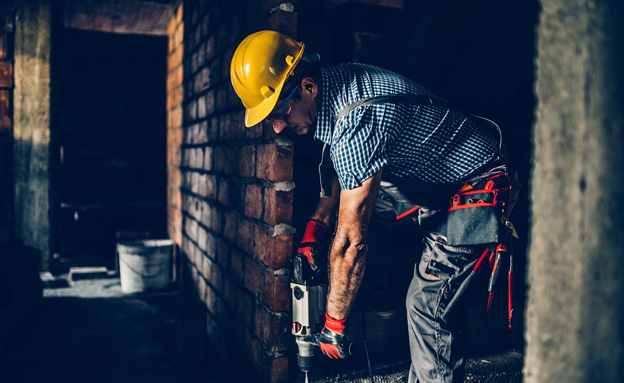 construction worker using power tools using decibullz hearing protection
