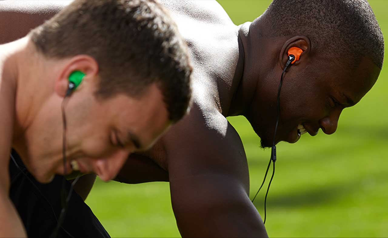 athletes running track wearing decibullz headphones