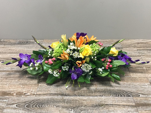 Spring Fling Centerpiece showcases lots of brightly colored flowers such as roses, lilies, iris, hydrangea and glads in a low container in Rockville MD, Palace Florists
