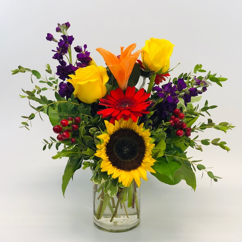 Randolph Chic showcases roses, stock, berries, sunflower and seeded eucalyptus in a clear cylinder in Rockville MD, Palace Florists